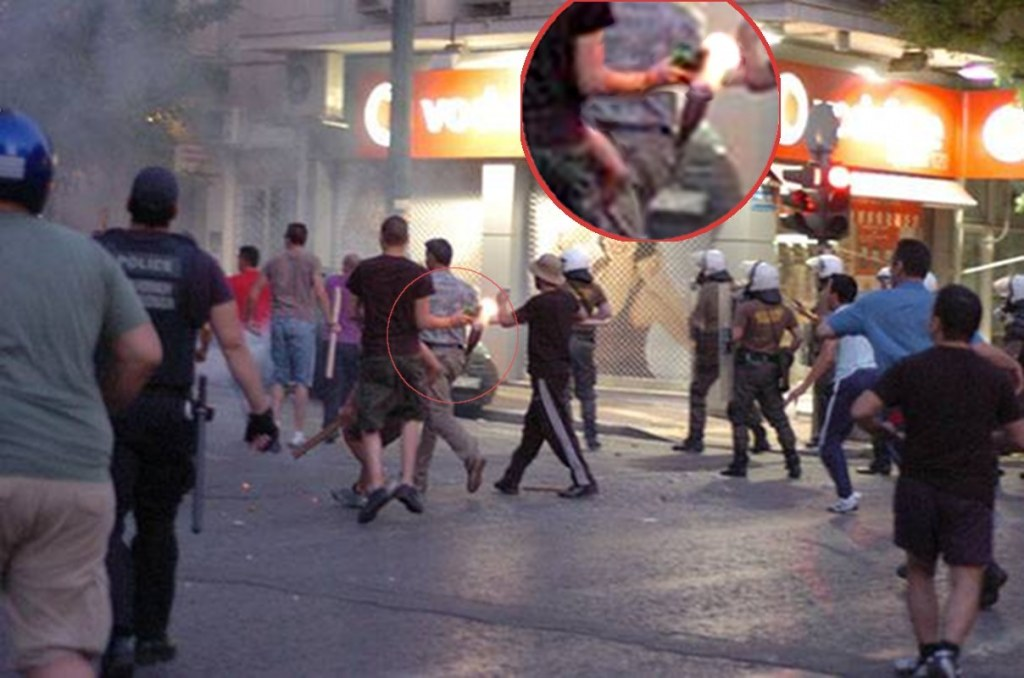 an Eleftherotypia newspaper photo reproduced at Athens Indymedia, showing some fascist attempting to throw a molotov from within the riot police ranks